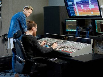 Audio engineer choosing sounds for track together with musician