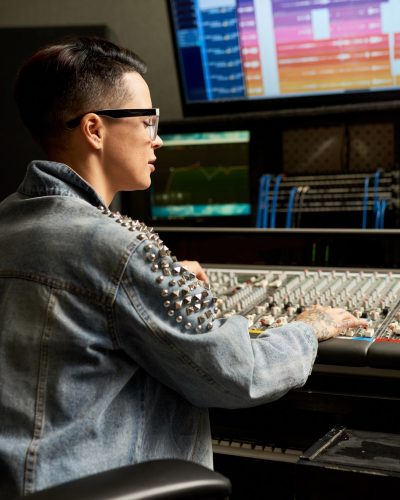 Concentrated audio engineer adjusting mixer in studio