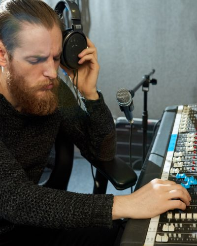 Concentrated music designer regulating sounds in studio