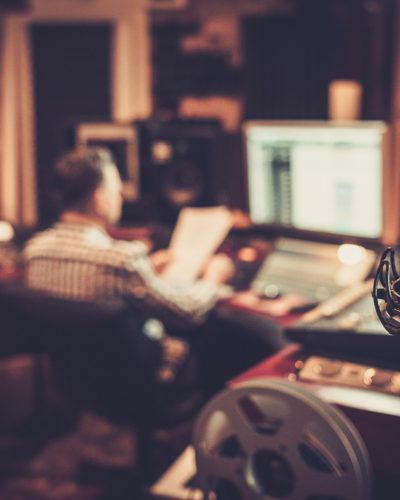 Sound engineer and producer working together at mixing panel in